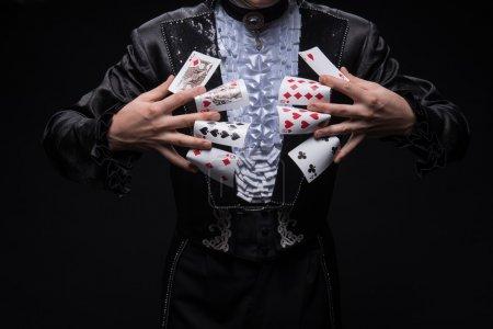 Photo pour Portrait semi-long de jongleur portant un costume noir intéressant et une chemise blanche tenant des cartes entre ses doigts. Isolé sur fond noir - image libre de droit