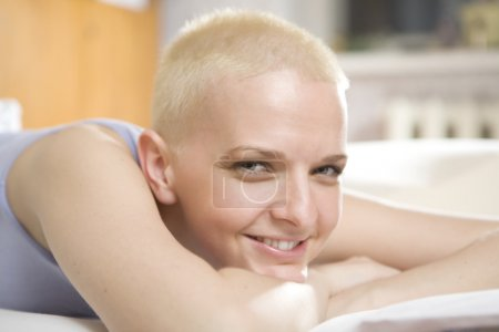 portrait of short hair blond serious woman in bedroom