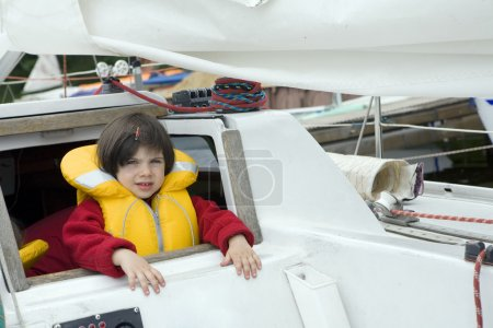 Little cute girl in life jacket on yacht