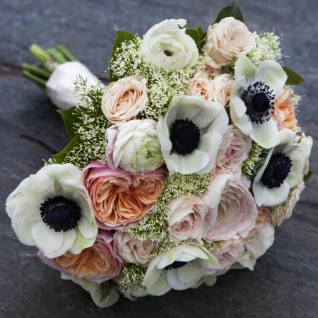 Wedding bouquet of pink roses and white anemone and pink ranunculus lying on wooden floor