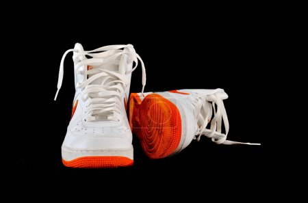 Photo for Pair of high-top classic Nike AF-1 Air Force 1 white leather basketball shoes sneakers, isolated on black - Royalty Free Image