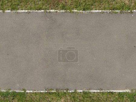 texture de nouveau, route asphaltée dans ton gris avec de l'herbe sur les bords