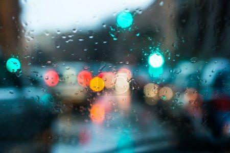 Photo pour Lumière floue des voitures vues à travers un pare-brise mouillé avec quelques gouttes de pluie sur elle tôt le matin d'une journée pluvieuse. Ratio horizontal . - image libre de droit