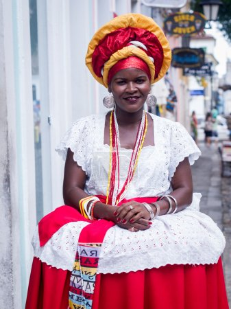 SALVADOR, BRAZIL - JUNE 31: Woman dressed in the traditional clothes of Bahia encourages tourists to enter souvenir shops in Salvador, Brazil on June 31, 2012. Women from Bahia are called Baianas