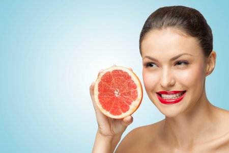 Photo for A creative portrait of a beautiful girl holding a red grapefruit sexually under her chin. - Royalty Free Image