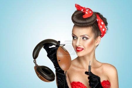 Photo pour La photo rétro d'une jolie pin-up girl qui tient des écouteurs vintage et veut écouter la musique . - image libre de droit