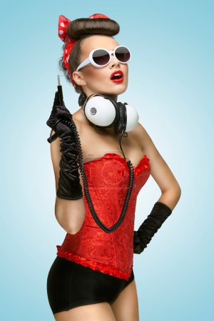 Photo for The pin-up photo of a cute girl in sunglasses with unplugged music headphones. - Royalty Free Image
