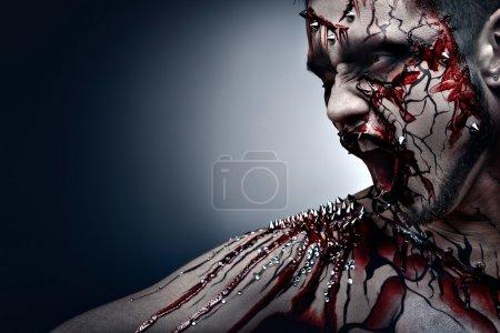 Foto de Un concepto de halloween espeluznante de un moro gritando de dolor con un piercing y sangriento arte corporal. - Imagen libre de derechos
