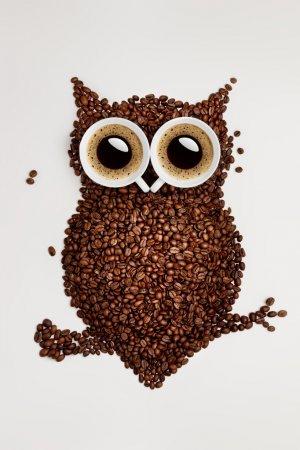 Photo pour Une chouette drôle, faite de grains de café torréfiés et deux tasses. - image libre de droit