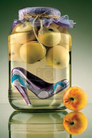 Photo pour Un gros plan d'une chaussure à la mode de talons préservé dans un bocal en verre avec pommes. - image libre de droit