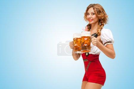 Photo pour Jeune femme suisse sexy excitée portant un short de pull rouge avec des bretelles sous une forme de dirndl traditionnel, servant deux tasses de bière sur fond bleu . - image libre de droit