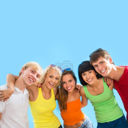 Photo pour Adolescents heureux embrassant ensemble sur fond bleu - image libre de droit