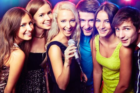 Photo for Young people singing into microphone at party - Royalty Free Image