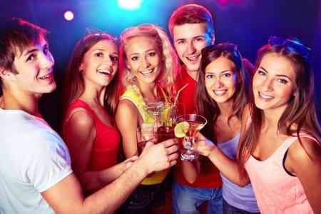 Photo pour Heureux groupe de jeunes amis cliquetis par des lunettes avec l'autre - image libre de droit