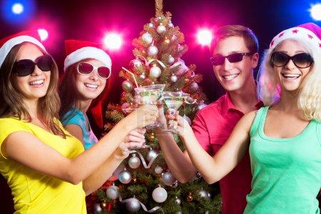 Photo pour Heureux les gens cliquetis par des lunettes autour du sapin de Noël - image libre de droit