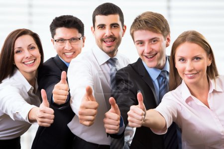 Photo pour Portrait de gens d'affaires heureux debout dans le bureau montrant pouce vers le haut - image libre de droit