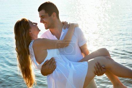 Photo pour Joyeux jeune couple profitant d'une plage solitaire - image libre de droit