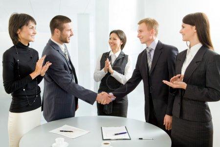 Photo pour Des collègues d'affaires serrent la main et applaudissent - image libre de droit