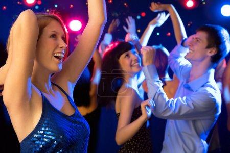 Photo pour Belle fille dansant à une fête avec vos amis - image libre de droit