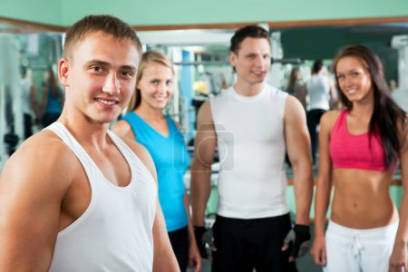 Fitness instructor with gym people