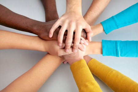 Photo for High view of team of friends showing unity with their hands together - Royalty Free Image