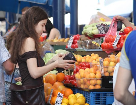 Shopping at the market. Girl is buying fruits on a market. Woman is counting if she has enough money for the purchase.