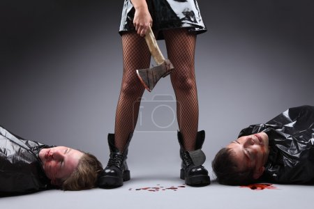Crime. Woman power and feminism concept. A woman with an axe covered in blood, two men lying down next to her feet. Dominancy of women over men. Matriarchy.