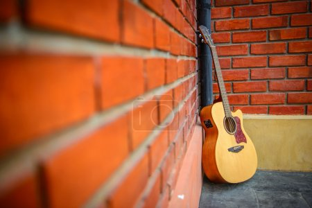 Photo for Guitar put on the floor with red brick background at the coffee shop. - Royalty Free Image