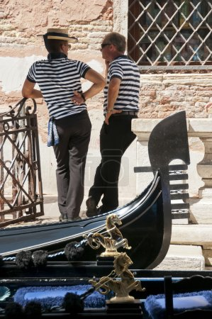 Gondoliers relaxing and chatting by their gondolas