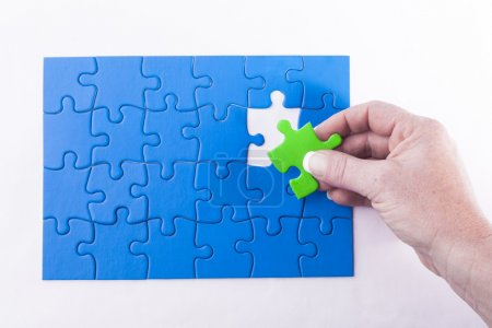 Woman's hand placing Jigsaw puzzle piece off different color sig