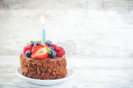 chocolate birthday cake with candle, raspberries, blueberries an
