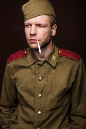 Second world war russian soldier smoking cigarette and looks at something