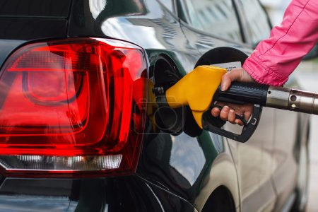 Woman filling up car at petrol station black car