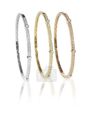Set of three colored gold diamond bangle bracelets...