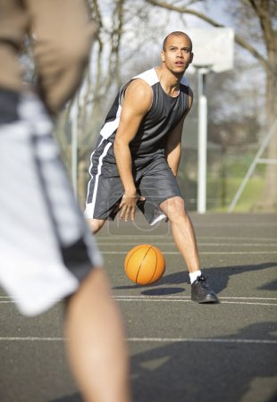 Basketball player bouncing the ball whilst looking to the hoop in the middle of a one on one.