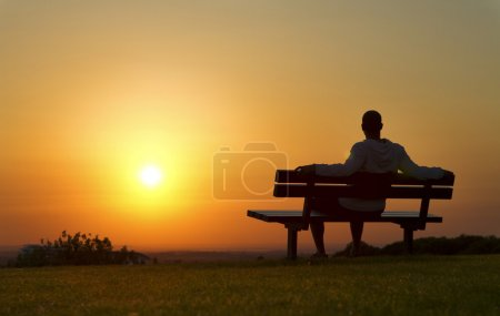 Man on a bench at sunset