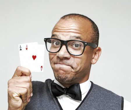 Brainy looking man holding up a strong poker hand of a pair of Aces