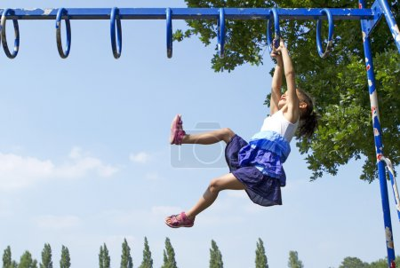 Young girl playing on monkey bars in an outdoor playground on a bright sunny day