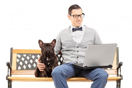 Man sitting with dog and on laptop