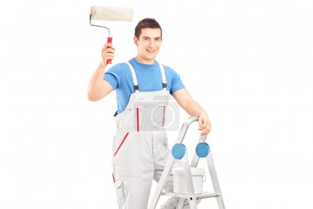 Photo for Male painter holding a roller and standing on a ladder isolated on white background - Royalty Free Image