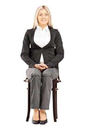 Photo pour Femme d'affaires blonde confiante en costume assise sur une chaise en bois isolée sur fond blanc - image libre de droit