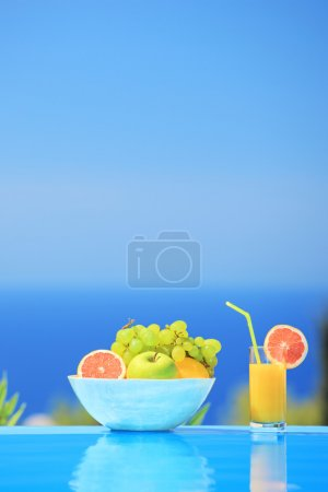 Juice and bowl of different fruits