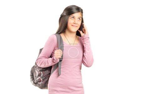 Photo pour Écolière parlant sur un téléphone mobile isolé sur fond blanc - image libre de droit