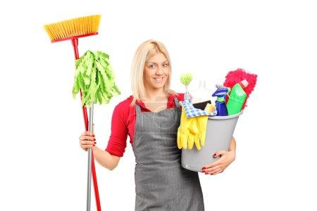 Photo pour Nettoyant féminin tenant un seau avec des fournitures de nettoyage isolées sur fond blanc - image libre de droit