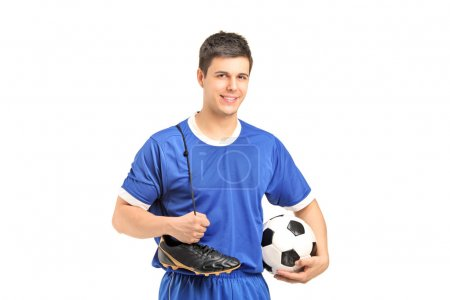 Footballer holding shoes and football