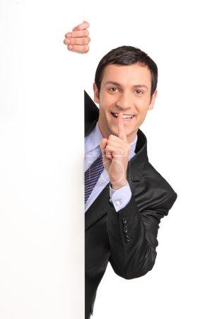 Photo pour Homme d'affaires en costume gestuel silence avec le doigt sur la bouche, derrière un panneau blanc, isolé sur fond blanc - image libre de droit