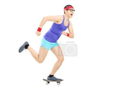 Nerdy guy riding small skateboard
