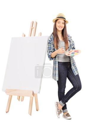 Photo pour Artiste féminine appuyée sur une toile vierge isolée sur fond blanc - image libre de droit
