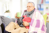 Nemocný muž na pohovce pít horký čaj