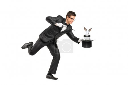 Photo pour Portrait complet d'un magicien tenant un chapeau haut de forme avec un lapin dessus isolé sur fond blanc - image libre de droit
